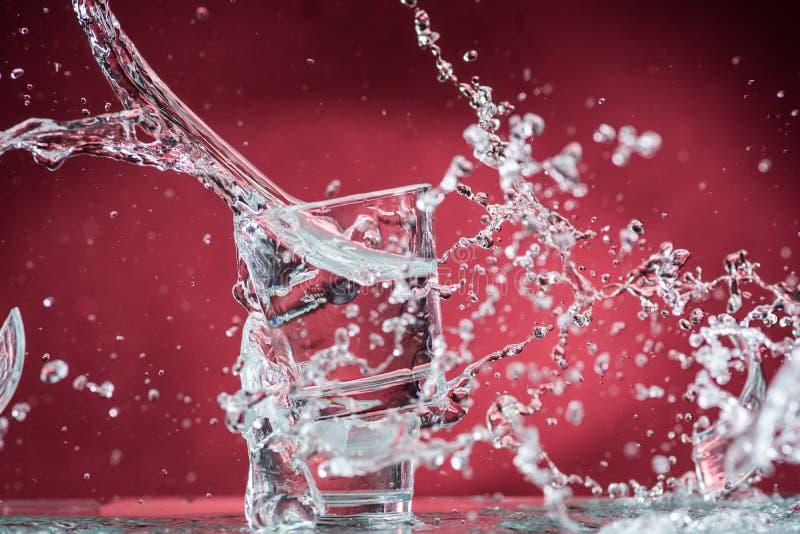 Dalende kleine glazen en het morsen van water op een blauwe achtergrond stock fotografie