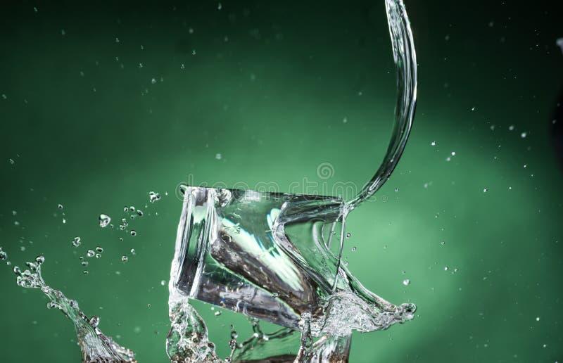 Dalende kleine glazen en het morsen van water op een groene achtergrond stock fotografie