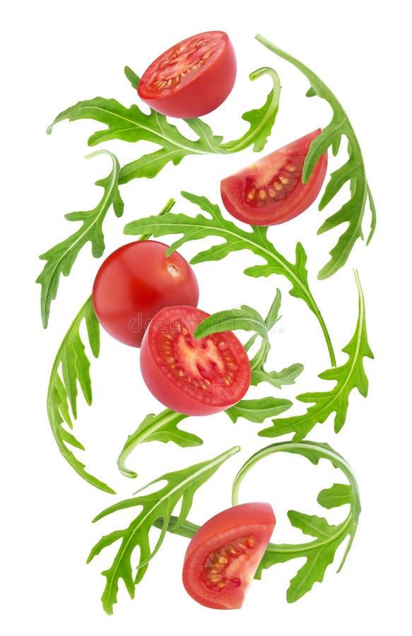 Dalende verse groenten Kersentomaten en rucola op witte achtergrond worden geïsoleerd die stock afbeelding