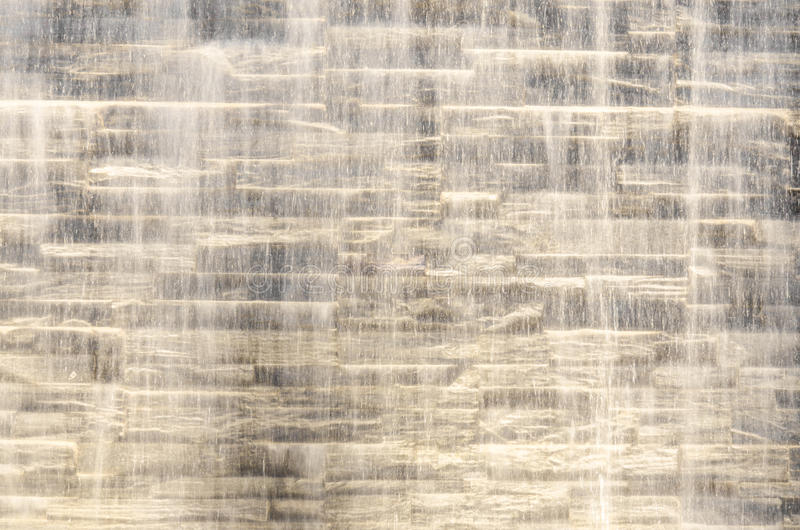 Dalende waterstroom tegen steenmuur royalty-vrije stock afbeeldingen