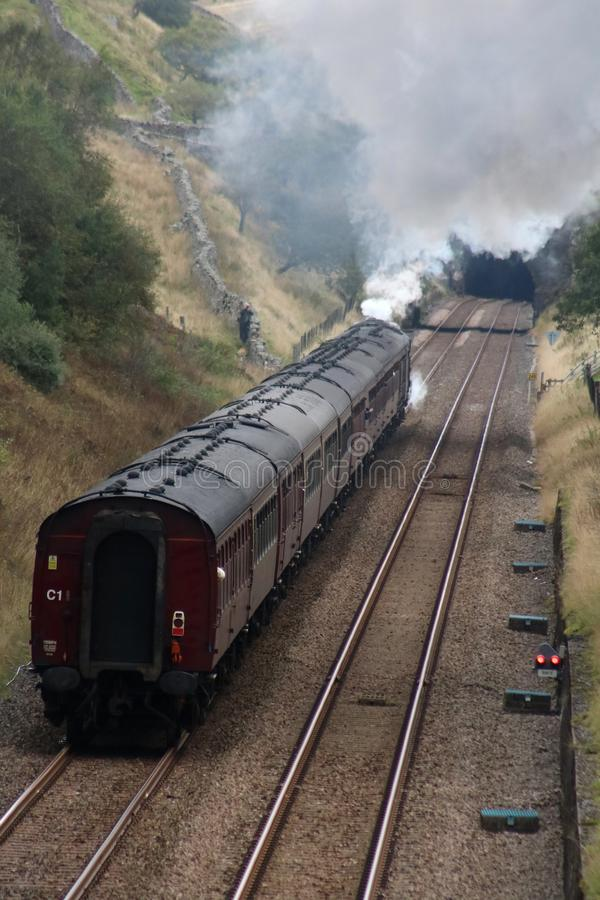 Dalesman steam train approaching Blea Moor Tunnel. LMS Royal Scot class preserved steam locomotive Scots Guardsman, number 46115, approaching Blea Moor tunnel on stock image