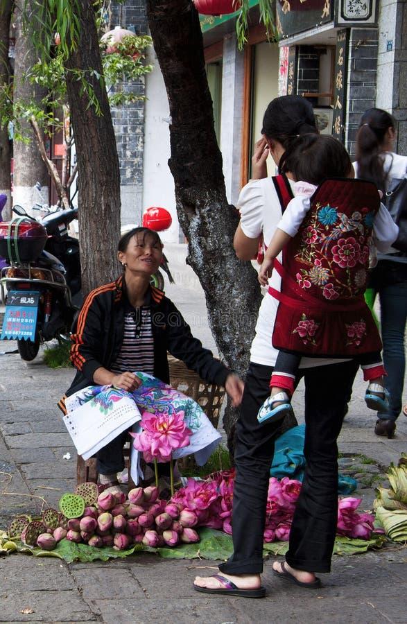 DALI, CHINA, EL 20 DE SEPTIEMBRE DE 2011: mujer que vende las flores de loto en t imagenes de archivo