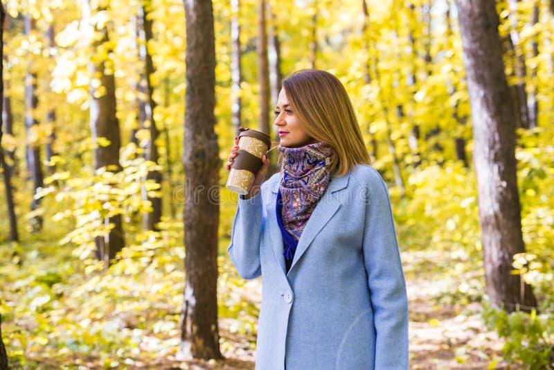 Daling, aard, mensenconcept - de jonge donkerbruine vrouw drinkt koffie in de herfstpark stock afbeeldingen