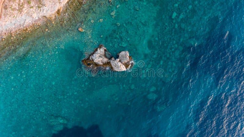 Daling onderaan mening van blauwe overzees met rotsen stock foto's