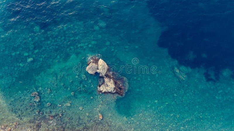 Daling onderaan mening van blauwe overzees met rotsen stock afbeeldingen