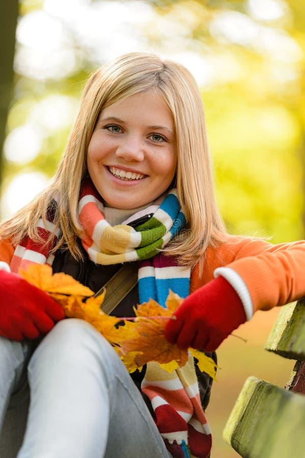 Daling van het de zittingspark van het de herfst de vrolijke jonge meisje royalty-vrije stock foto