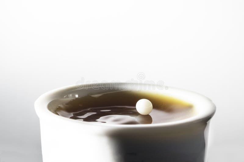Daling van melk het in evenwicht brengen op koffie stock foto's