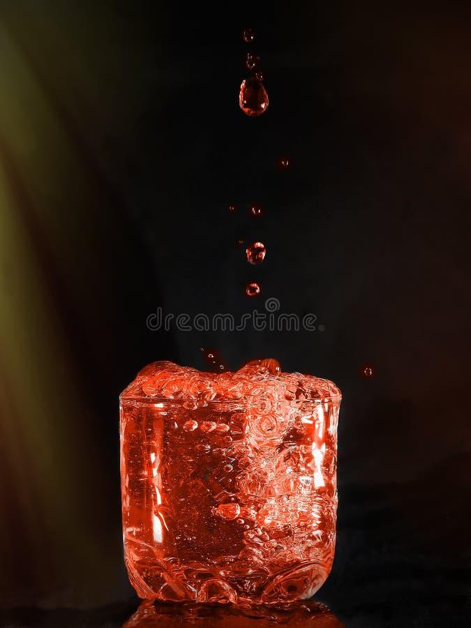 Dalingen die in een glas vallen stock foto