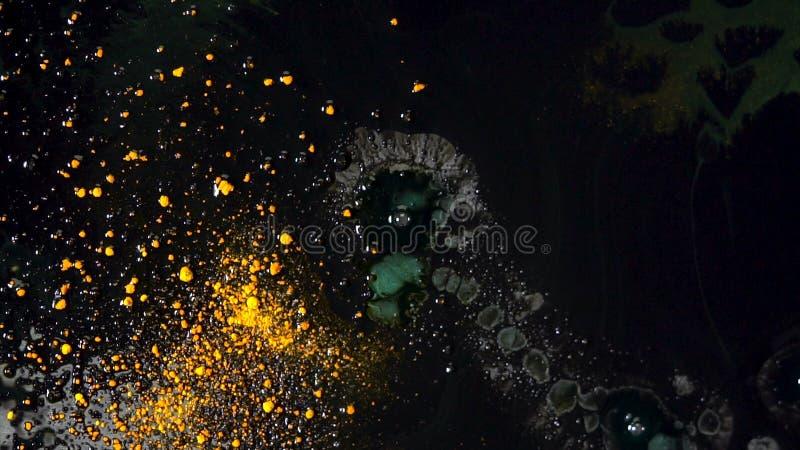Dalingen die van vloeibare zeep in zwarte substantie met gele droge inkt vallen die op de oppervlakte drijven Kleurrijke reactie  royalty-vrije stock afbeeldingen