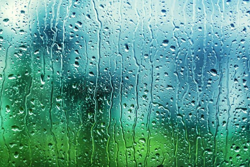 Dalingen en stromen van water op glas stock afbeeldingen