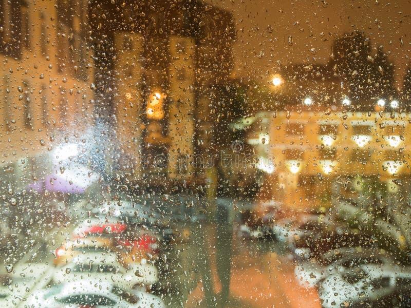 Dalingen op het glas van de regen in de avond tegen de achtergrond van huizen royalty-vrije stock afbeeldingen