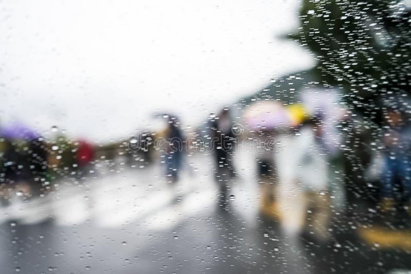 Dalingen van regen op blauwe glasachtergrond De Lichten van straatbokeh uit Nadruk Kleurrijke paraplu's Autumn Abstract Backdrop royalty-vrije stock afbeelding