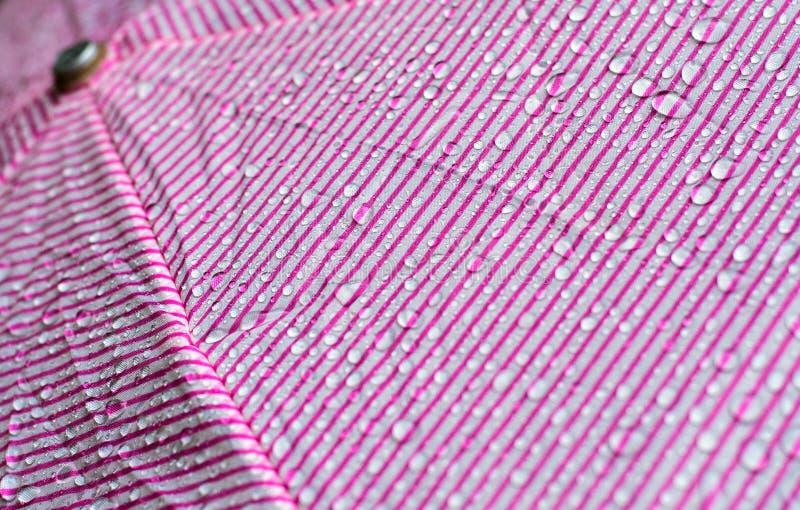 Dalingen van water na regen op een roze paraplu royalty-vrije stock afbeelding