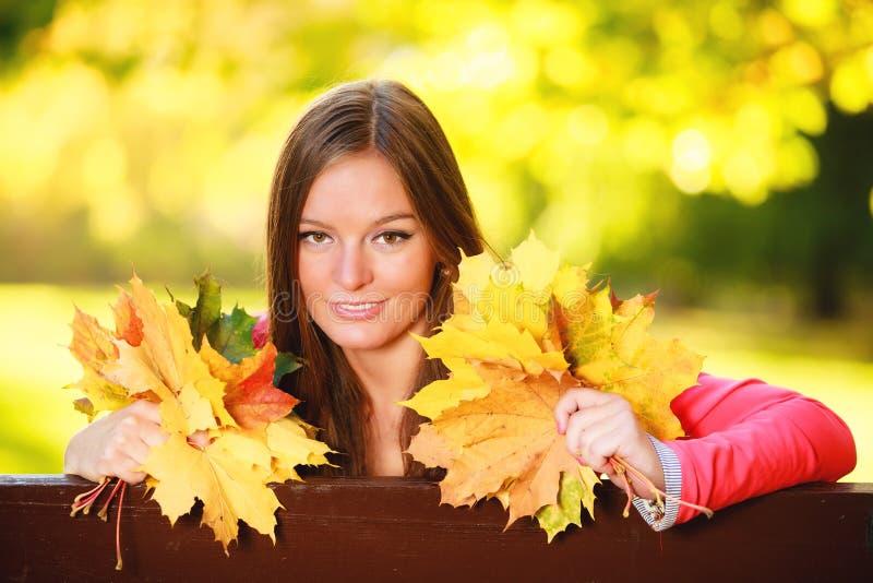 Dalingsseizoen. De vrouw die van het portretmeisje herfstbladeren in park houden royalty-vrije stock afbeelding