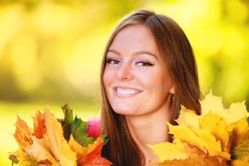 Dalingsseizoen. De vrouw die van het portretmeisje herfstbladeren in park houden royalty-vrije stock fotografie