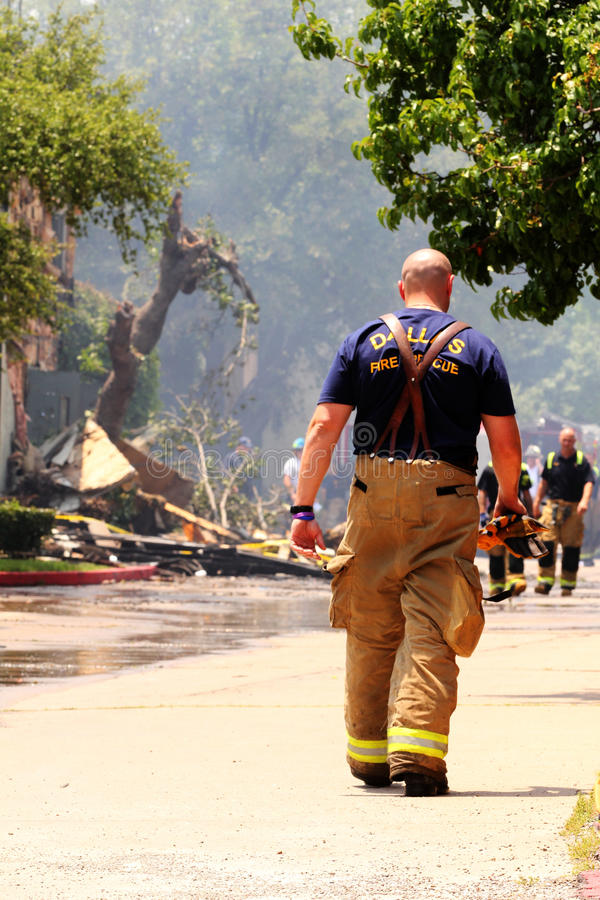 Dallas fire fighter dies. Fire fighter in Dallas Texas fighting fire and cleaning debris from a burning condo complex in north east Dallas royalty free stock images