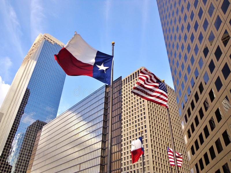 Dallas Flag and United States Flag Waving in the Wind - Downtown Houston, Texas. Low angle view of United States of America flag and Texas state flag in front of stock images