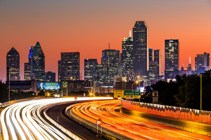 Dallas skyline at sunrise. Dallas skyline by night. The rush hour traffic leaves light trails on I-30 (Tom Landry) freeway