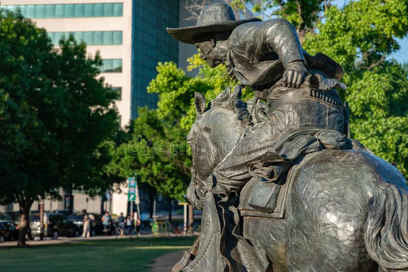 Dallas Teksas, Maj, - 7, 2018: Kowboja i longhornu krowy z bydłem w tle jako część punktu zwrotnego brązu bydła, zdjęcia royalty free