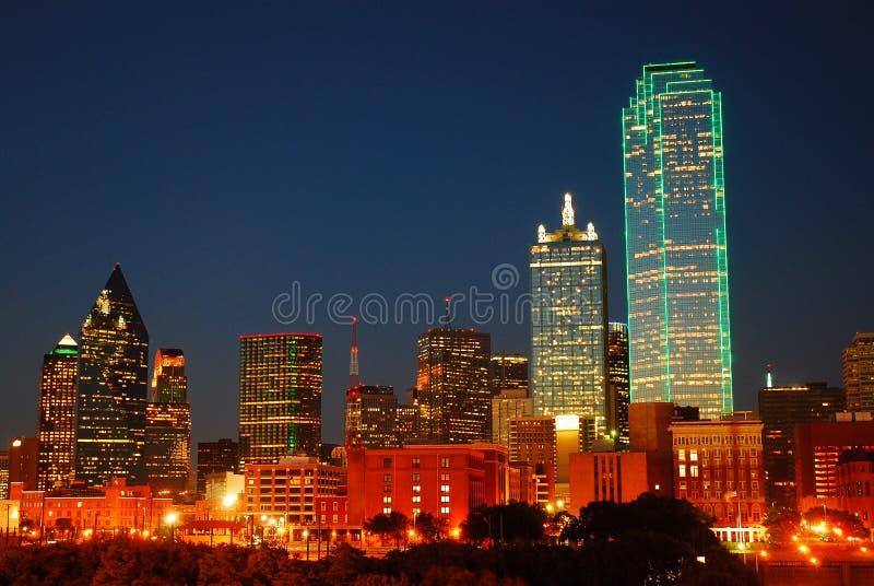 Dallas Texas Skyline brilla intensamente contra un cielo de la oscuridad imagen de archivo