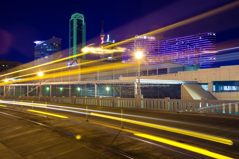 DALLAS, TX - DECEMBER 10, 2017 - Light trails from moving streetcar on the Houston Street with the city of Dallas in background. The Dallas Streetcar is a 2.45 stock photo