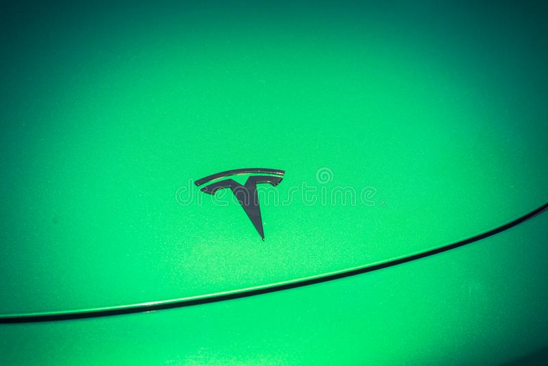 Green car hood cover with Tesla logo close-up stock image