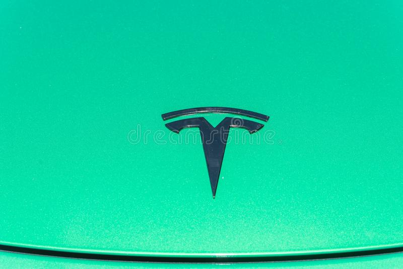 Green car hood cover with Tesla logo close-up stock photo