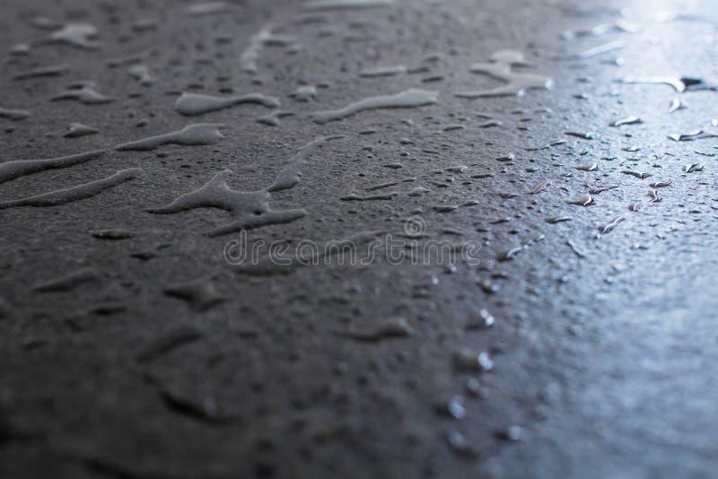 Dalle noire crue et rugueuse de granit humide avec de l'eau Baisses et correction photos stock