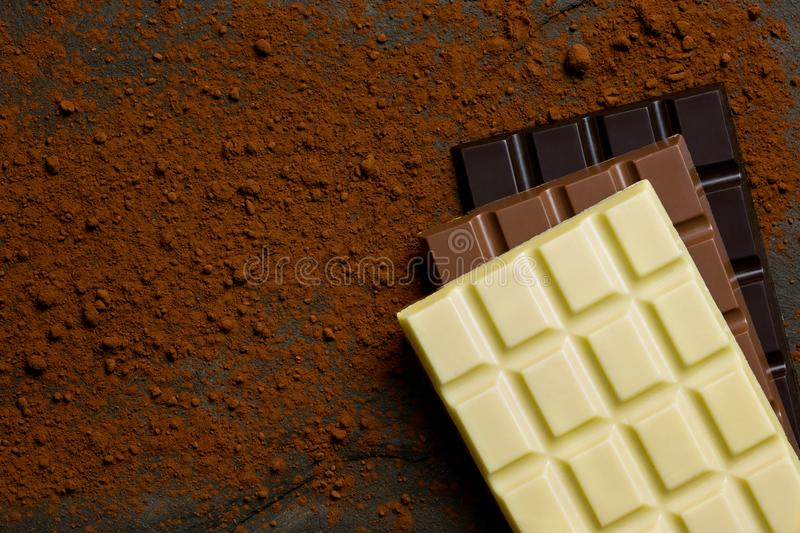 Dalles de blanc, de lait et de chocolat foncé sur l'un l'autre sur une ardoise noire époussetée avec la poudre de cacao d'en haut photos libres de droits
