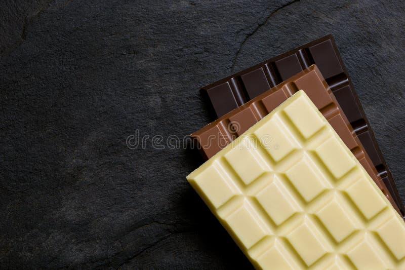 Dalles de blanc, de lait et de chocolat foncé sur l'un l'autre sur une ardoise noire d'en haut L'espace pour le texte photo stock