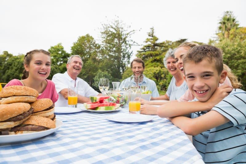 Dalsza rodzina ma gościa restauracji przy pyknicznym stołem outdoors obraz stock