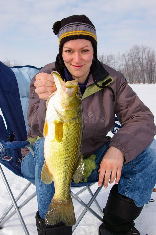 Dam Angler Fisherwoman Holds en Largemouth Bass Caught Ice Fishing royaltyfri fotografi