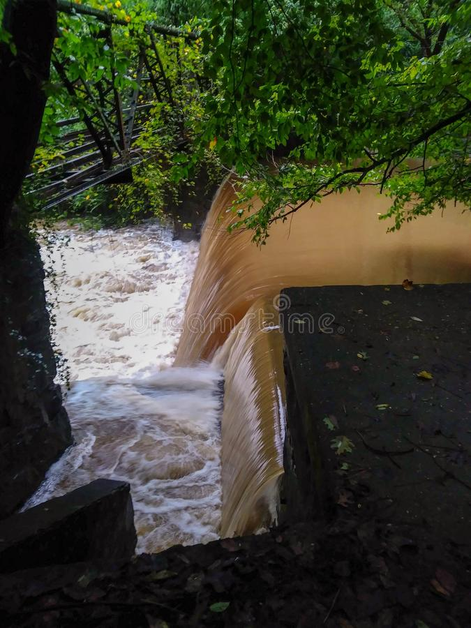 Old Historic Hydroelectric Dam and Horse and Buggy Bridge over flooded creek. Dam after a hard rain. dams, hydroelectric, hydoelectricity, mill, mills, power royalty free stock images