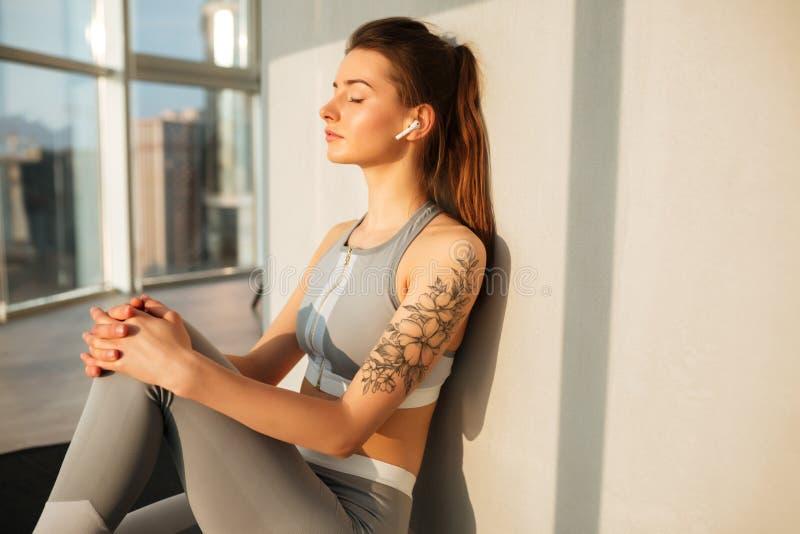 Dam i damasker som sitter på matt lyssnande musik för yoga i hörlurar som stänger dreamily hennes ögon royaltyfri fotografi