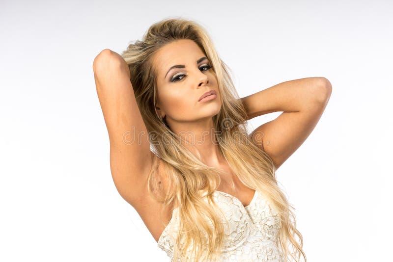 Dam i den vita blusen som poserar i studio Härlig lång elegant kvinna för blont hår i skjorta Skönhetstående av modellmode arkivbild