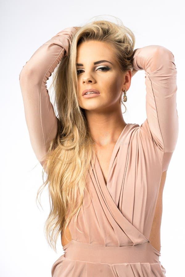 Dam i den vita kappan som poserar i studio Härlig elegant kvinna, långt blont hår i aftonklänning Skönhetstående av modernt mode royaltyfria bilder