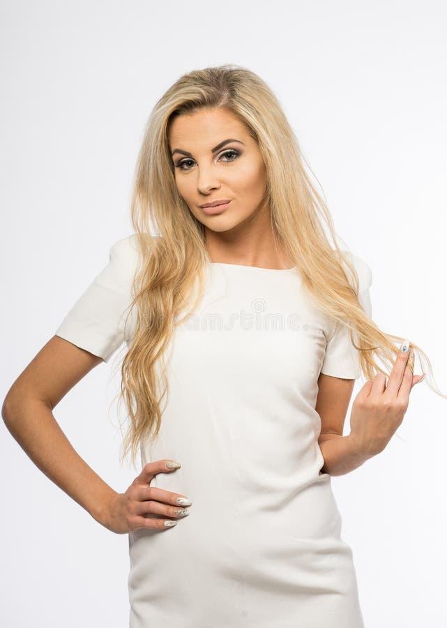 Dam i den vita kappan som poserar i studio Härlig elegant kvinna, långt blont hår i aftonklänning Skönhetstående av modernt mode fotografering för bildbyråer