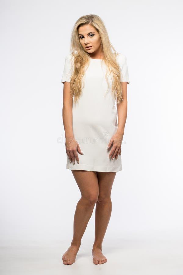 Dam i den vita kappan som poserar i studio Härlig elegant kvinna, långt blont hår i aftonklänning Skönhetstående av modernt mode royaltyfri foto
