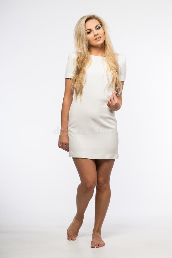 Dam i den vita kappan som poserar i studio Härlig elegant kvinna, långt blont hår i aftonklänning Skönhetstående av modernt mode royaltyfria foton