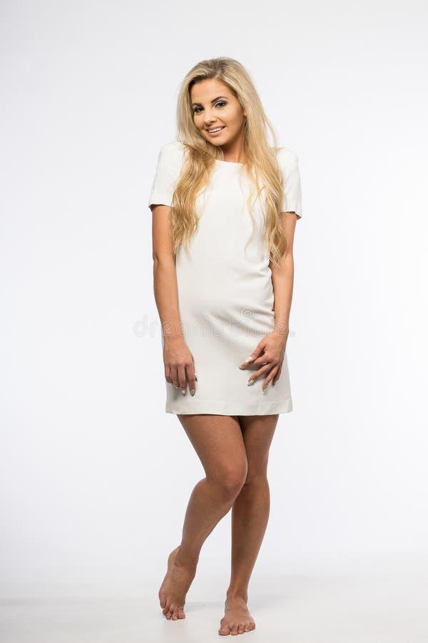Dam i den vita kappan som poserar i studio Härlig elegant kvinna, långt blont hår i aftonklänning Skönhetstående av modernt mode arkivfoto