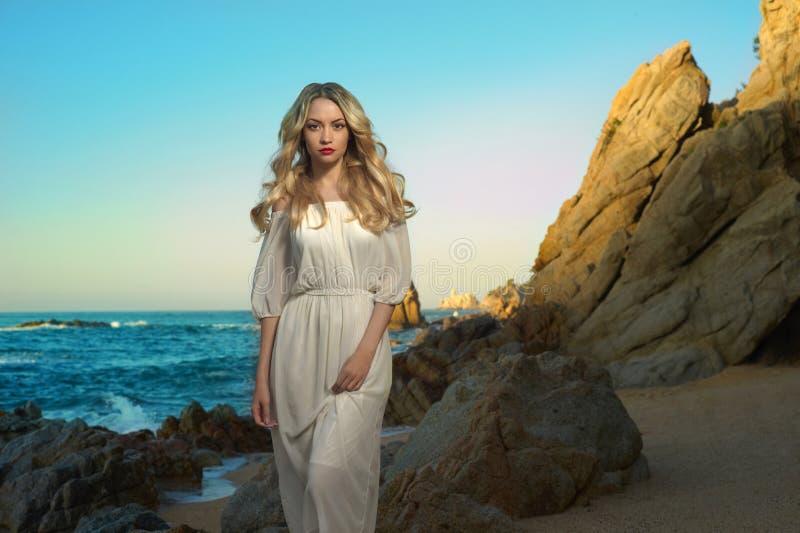 Dam i den vita klänningen på kusten arkivbilder