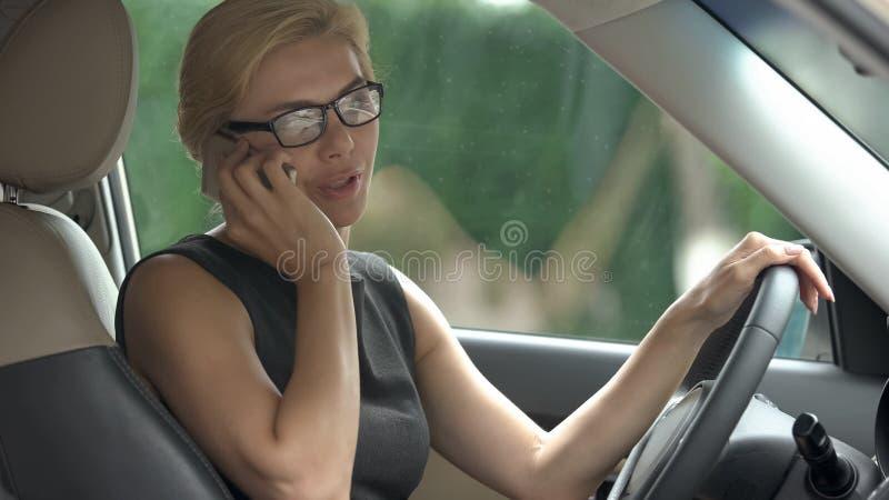 Dam i officiell klänning som talar på telefonen i bilen som skvallrar med vännen, nyheterna arkivfoto