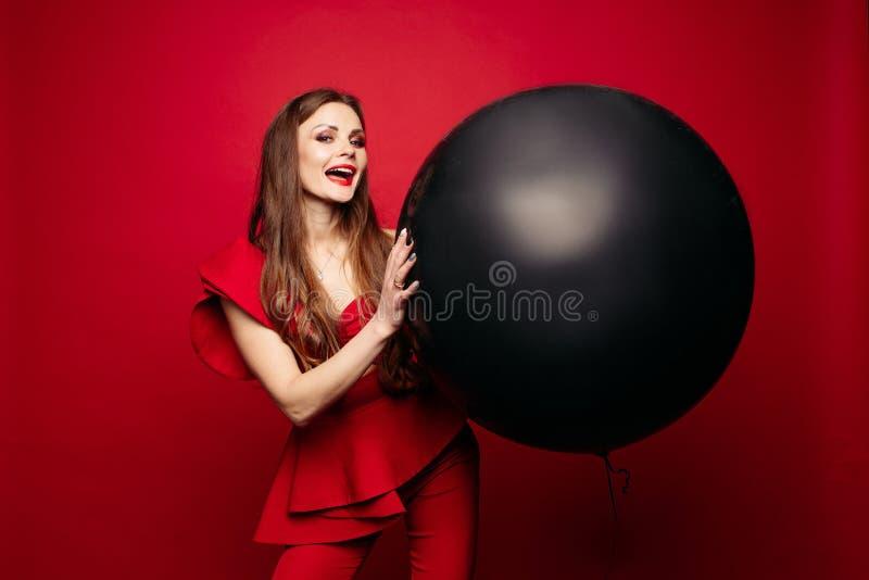 Dam i r?d dr?kt med l?ngt h?r som rymmer den stora svarta bollen fotografering för bildbyråer