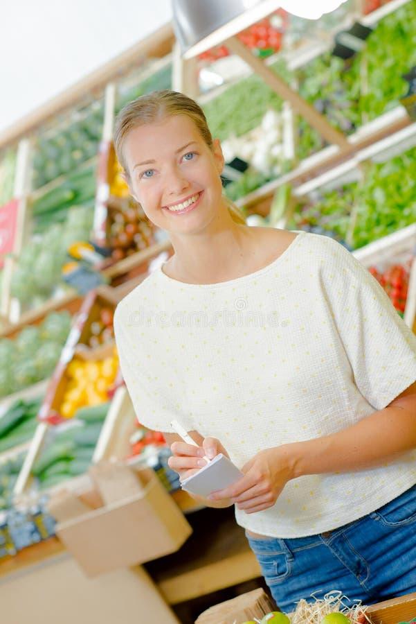 Dam i specerihandlare med listan arkivbilder