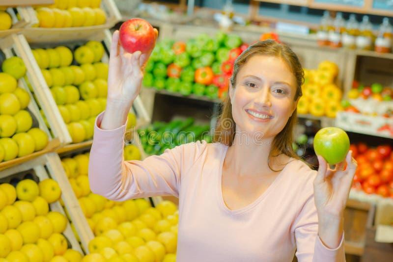 Dam i specerihandlare som rymmer två olika variationer för äpplen arkivbilder