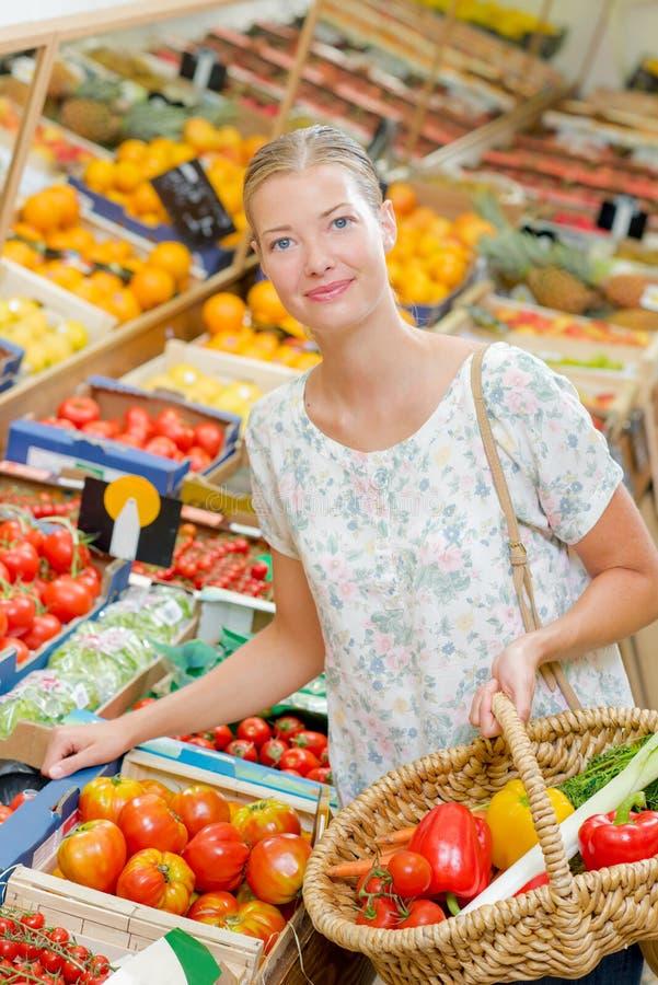 Dam i specerihandlare som väljer frukt och grönsaker royaltyfri foto