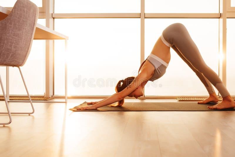 Dam i sportig överkant och damasker som hemma står och öva yoga över härlig fönstersikt arkivfoton