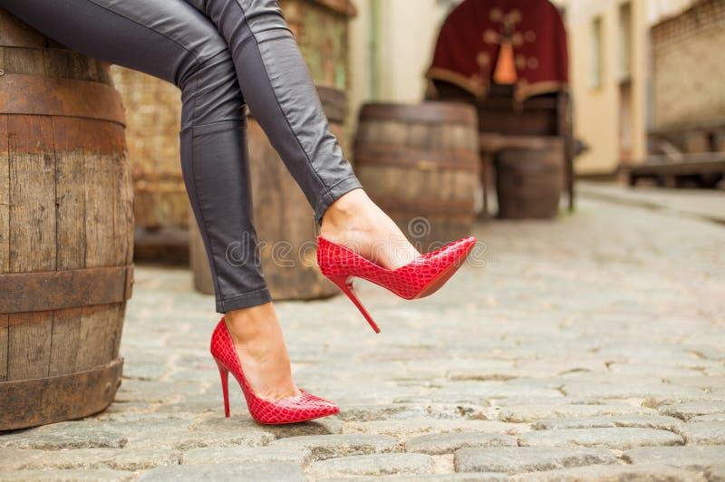 Dam i svarta läderflåsanden och röda skor för hög häl arkivbilder