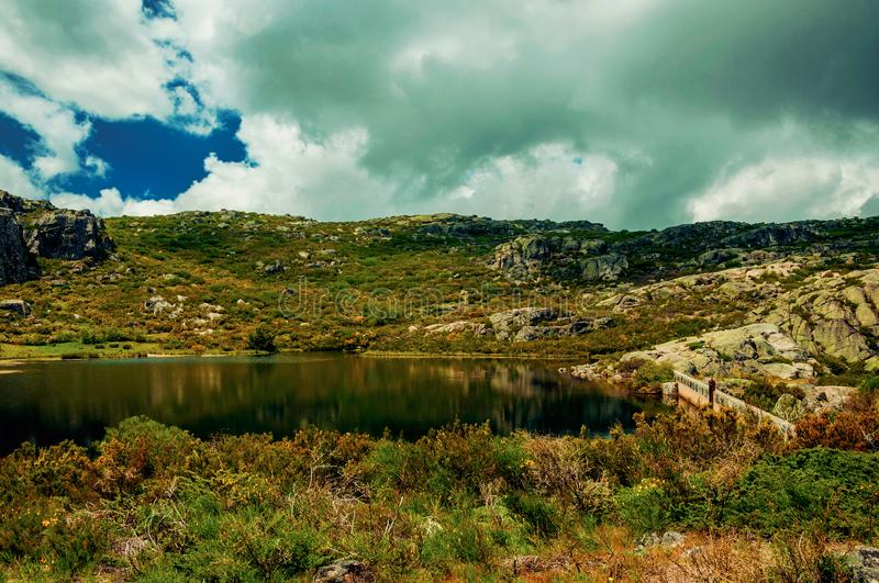 Dam lake among rocks and bushes on highlands. Dam lake at Covao dos Conchos among rocks and bushes on highlands, in a sunny day at the Serra da Estrela. The stock photos