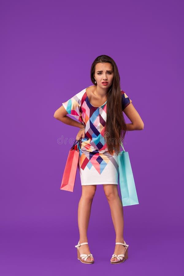 Dam med den trötta framsidan Flickan står på hållande shoppingpåsar för purpurfärgad bakgrund Kvinnan bär den trendiga klänningen arkivfoto